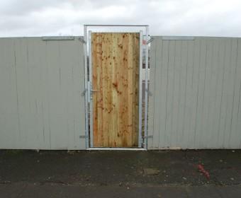 Eine Tür im Bretterzaun.